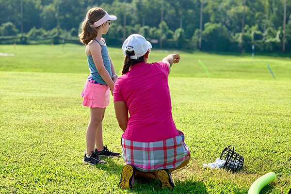 junior golfer getting advised from trainer